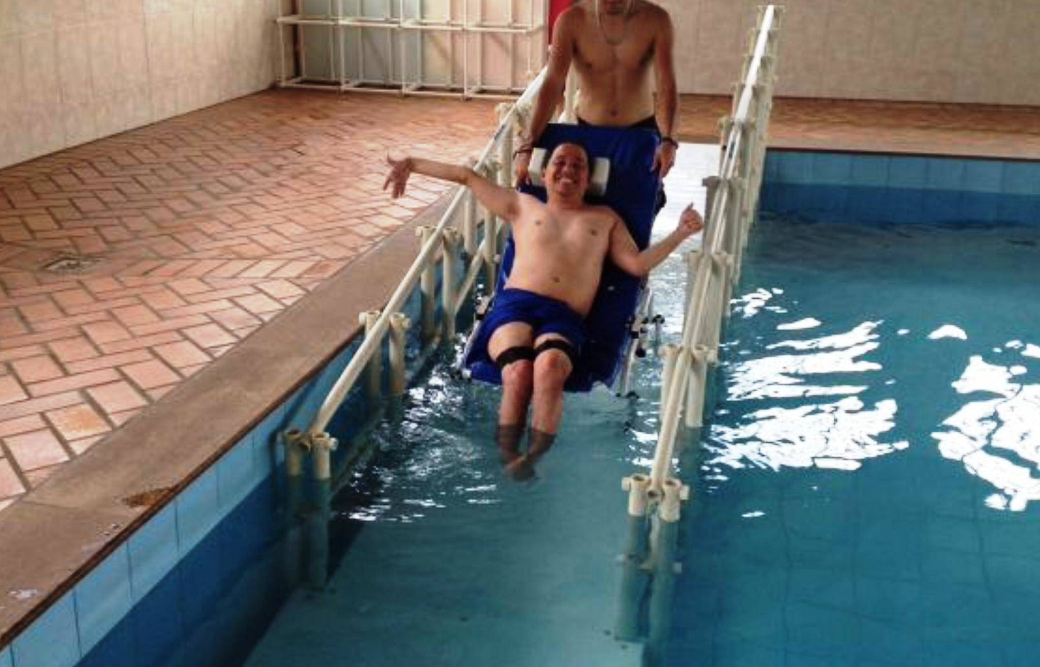 APAE SRPQ cadeirante descendo a rampa assistido por profissional